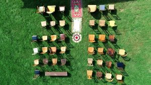 micro wedding video, 50 vintage chairs viewed from above on a green lawn with an aisle of vintage rugs