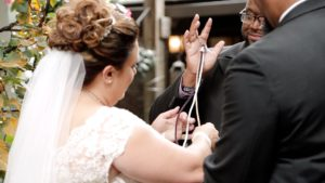 ceremony video still, bride and groom braiding a unity braid during their wedding ceremony