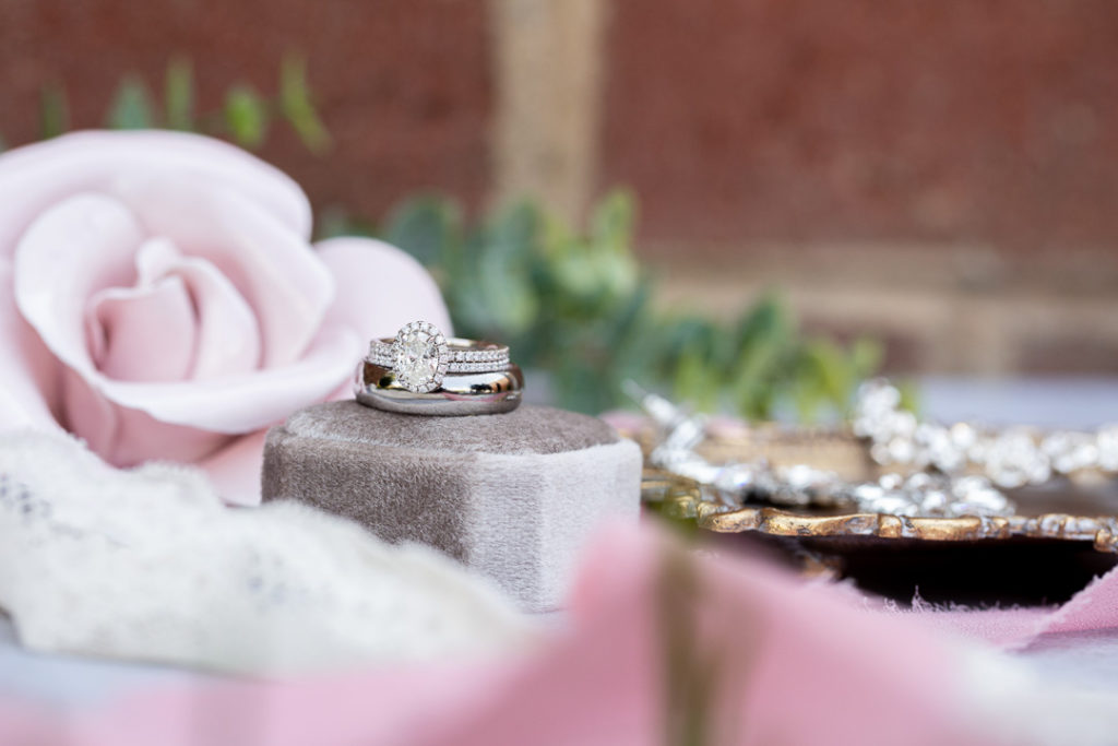 details on a wedding day including engagement rings perfume bottle and shades of pink