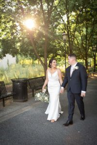 covid safe wedding, bride a groom holding hands and walking in front of the sun setting behind trees