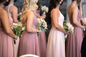 bridal party in shades of pink, holding bouquets, wearing navy COVID facemasks