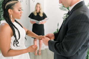 livestream wedding ceremony, bride with boxbraids and a sleeveless white dress exchanging ring with groom in a navy tux