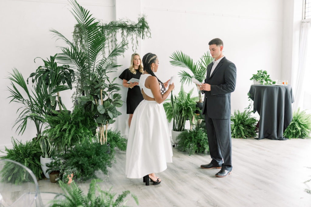 bride and groom exchanging vows in front of massive greenery display, microwedding ceremony
