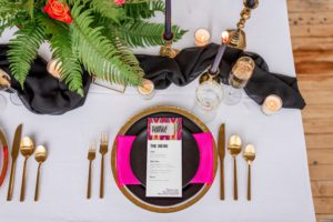 colorful wedding tablescape, white and black tablecloth with hot pink accents, gold silverware