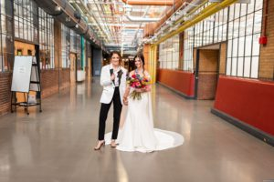 two brides, one in a white and black tux, one in an off the shoulder white gown, holding hands in the colorful industrial hallway at the Energy Innovation Center in Pittsburgh PA