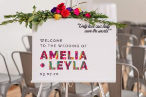 colorful wedding welcome sign with a swag of bright florals
