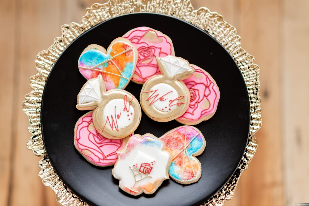 colorful collection of wedding cookies on a black and gold plate, we do wedding cookies