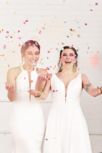 two brides smiling and laughing, celebrating their wedding with a confetti toss, lgbtq wedding