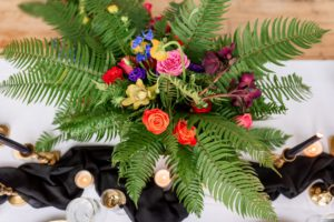 arrangement of bright and colorful flowers and green ferns on a white table with a black runner and candles